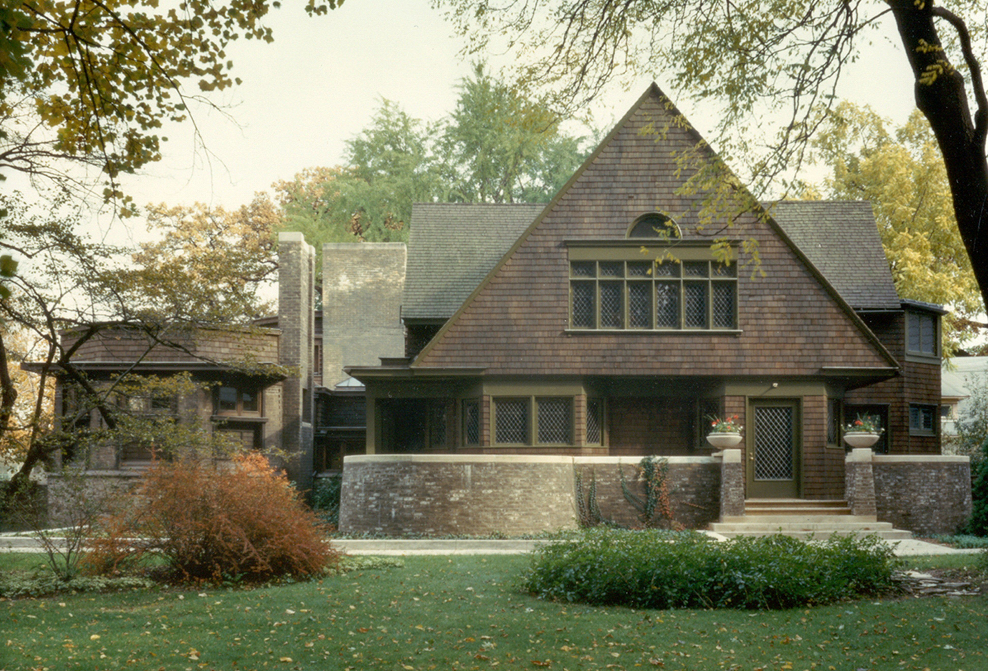 large front gable, brown shingles, large roof, curved stone wall