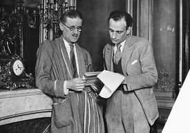 Author James Joyce (left) looks at a set of papers