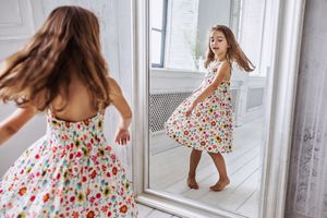 Little girl in summer dress turning around at the mirror