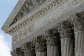 detail of stone portico, showing the tops of fluted columns, fancy capitals, a carved inscription (equal justice under law), dentils, and part of a pediment filled with sculture