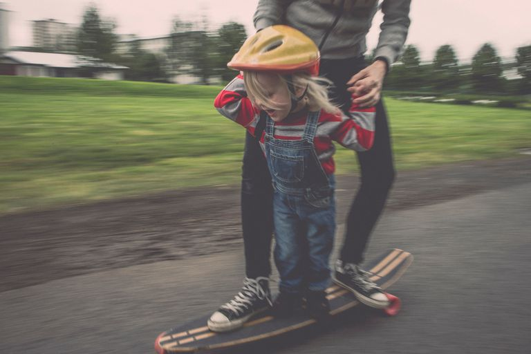 Father and child on a skateboard.