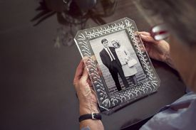 Elderly woman looking at old photograph