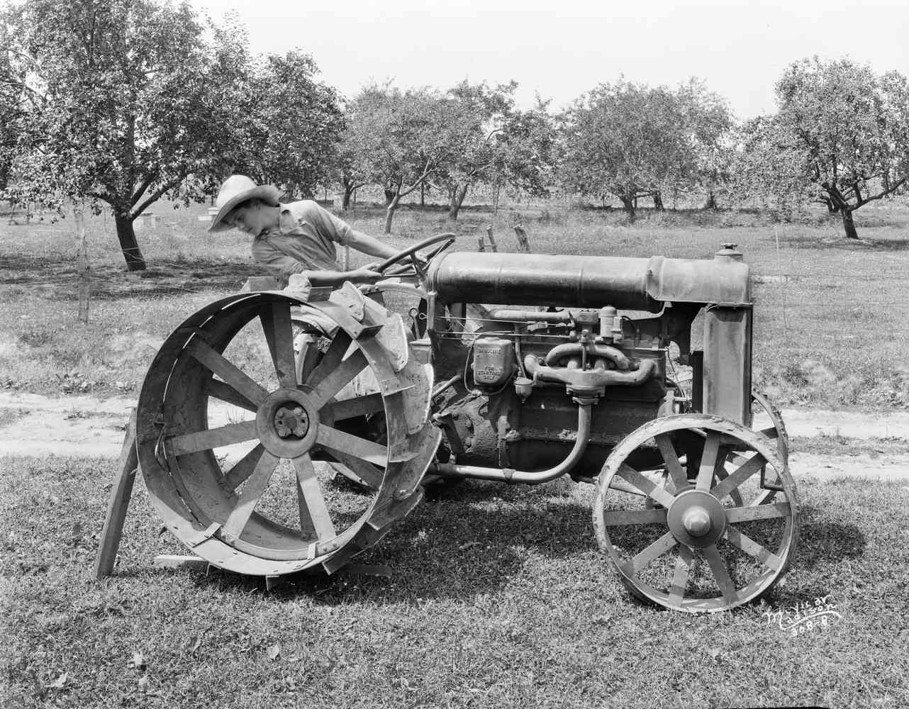 Right side view of a man sitting near an orchard, on a Fordson tractor.