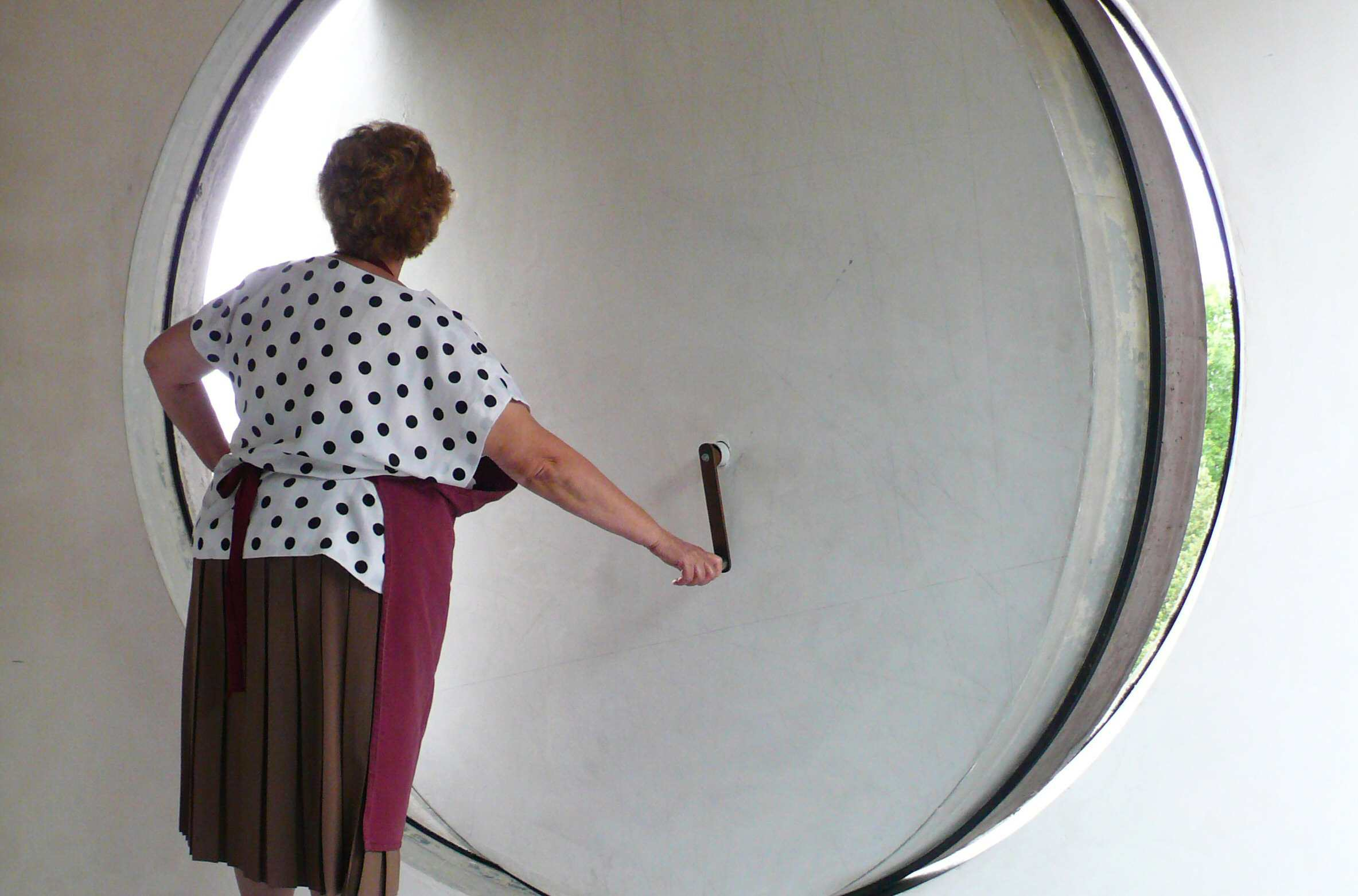 The Housekeeper turns a handle to open a portal window at Maison a Bordeaux designed by Rem Koolhaas