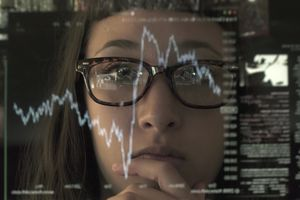 A computer screen showing statistical data is superimposed over an image of a woman wearing glasses.