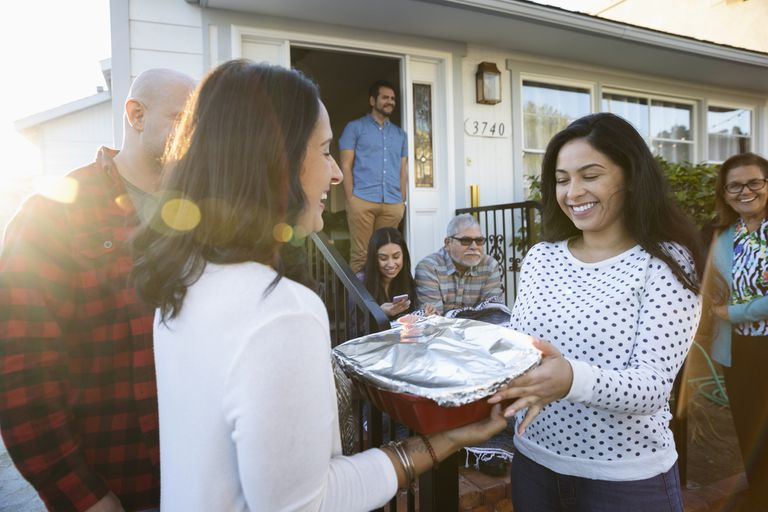 woman handing her neighbor a casserole