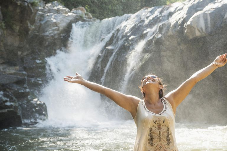 Joyful woman, arms outstretched, standing in front of waterfall