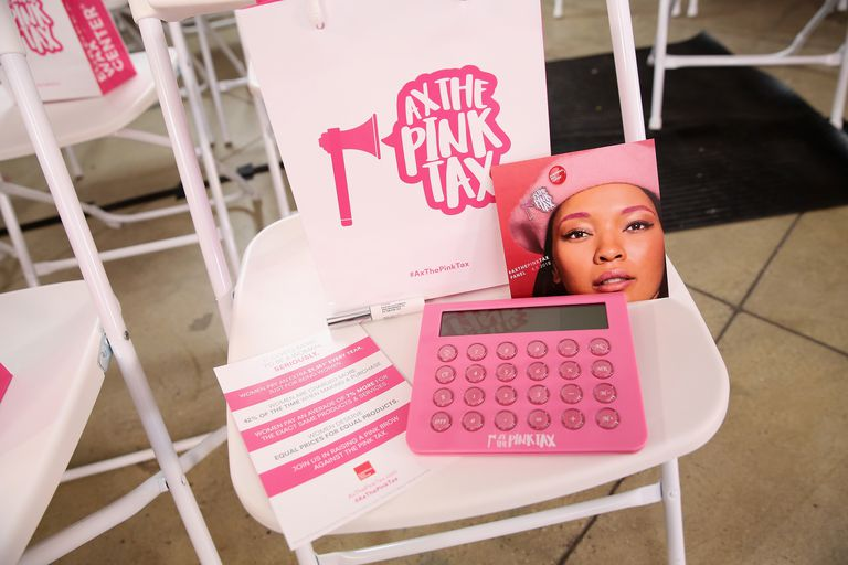 """A white gift bag with pink text reading """"Ax the Pink Tax"""", a pink calculator, and other items"""