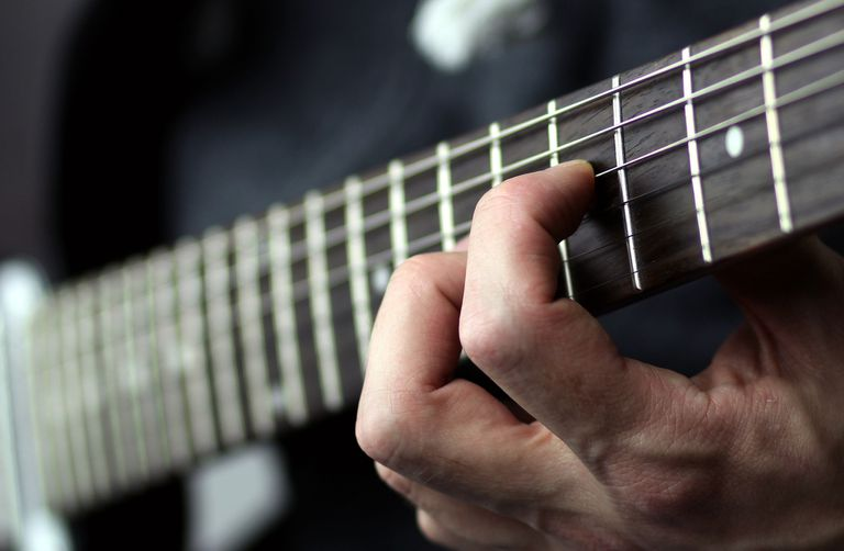 Fingers on a guitar fret