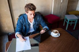 Young man sits at table with laptop and pen and paper