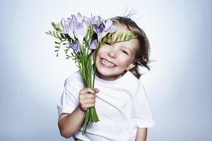 kid holding flowers and smiling