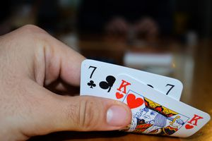 Cropped man's hand holding playing cards