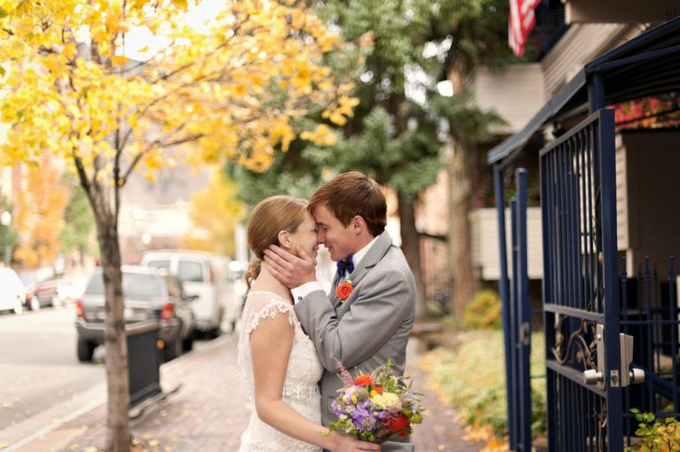 Bride and groom kissing on sidewalk