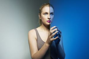 a woman staring ahead next to her reflection