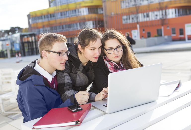 Three students using laptop outdoors