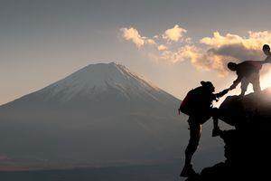Young hikers climbing up on the peak of mountain near mountain fuji in Japan