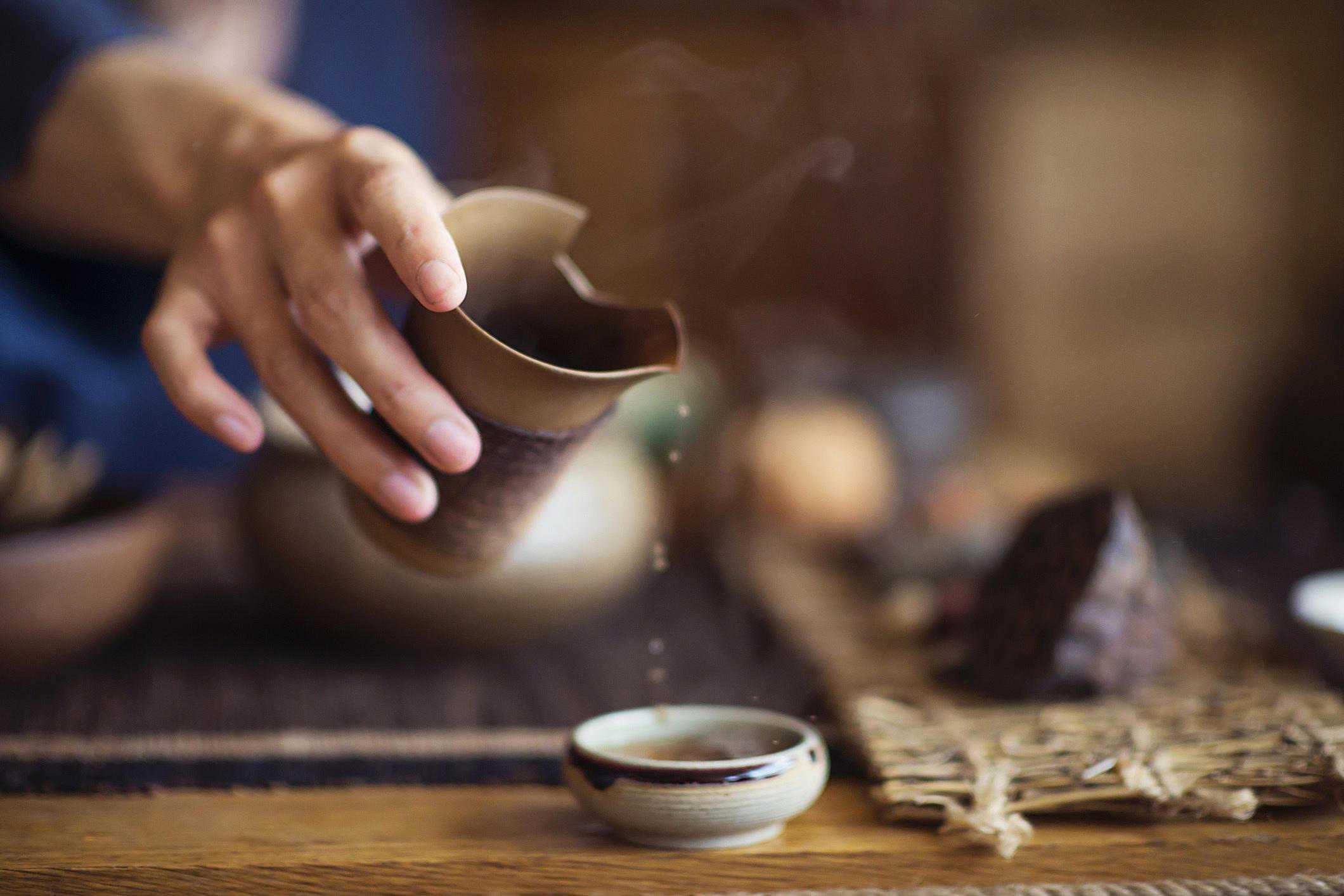 Serving Chinese tea into ceramic tea cups