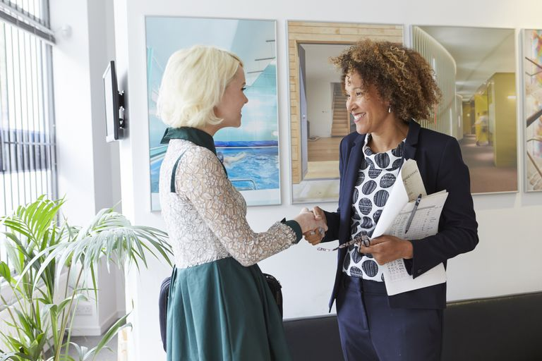 Female business women greeting each other in office lobby.