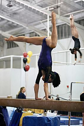 The gymnast in the foreground is performing on the balance beam f27d2bd8b