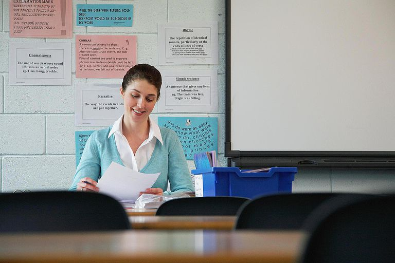 Female schoolteacher sitting at desk, reading paperwork, smiling