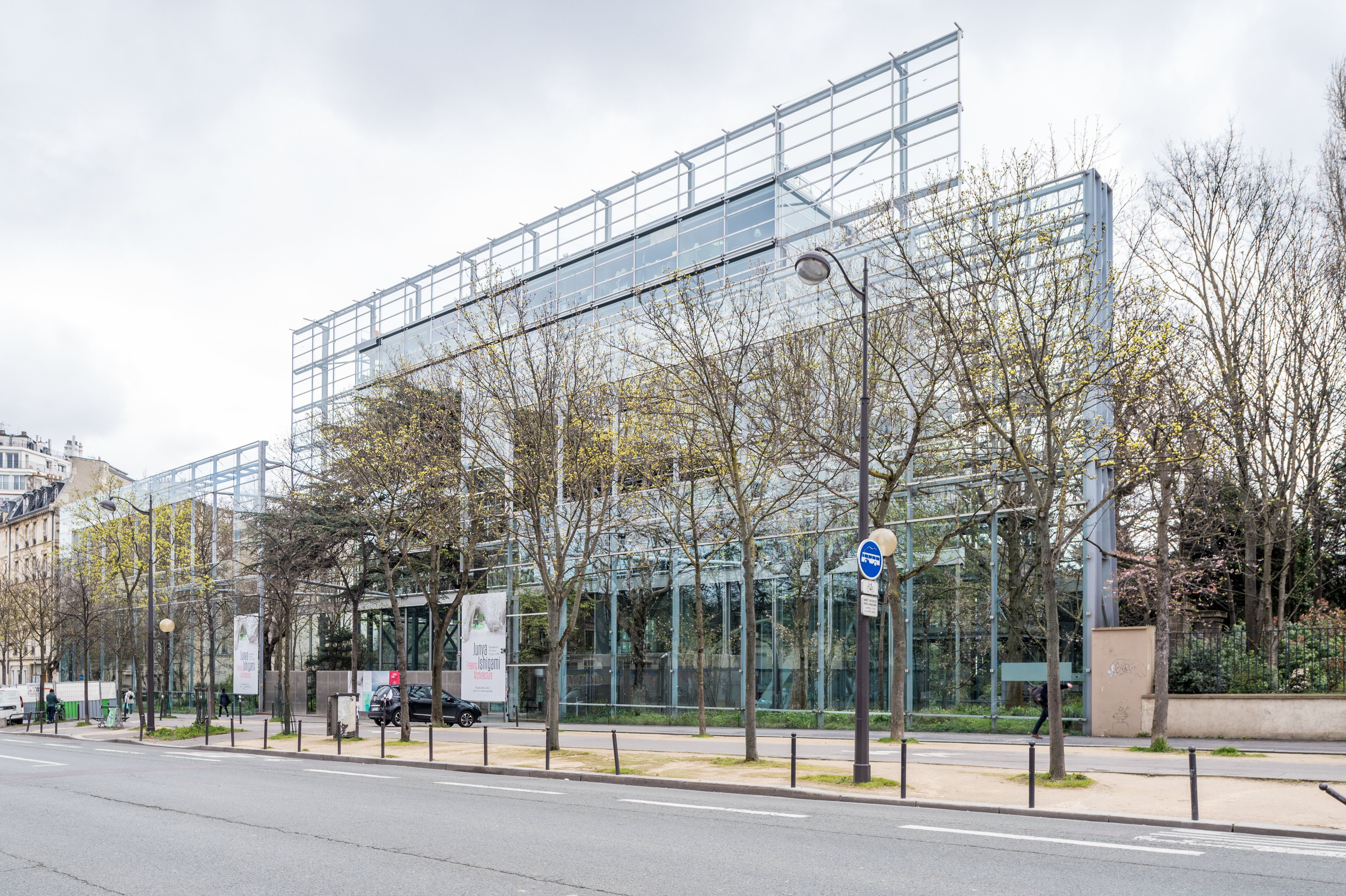 glass and metal facade on a tree-lined city street