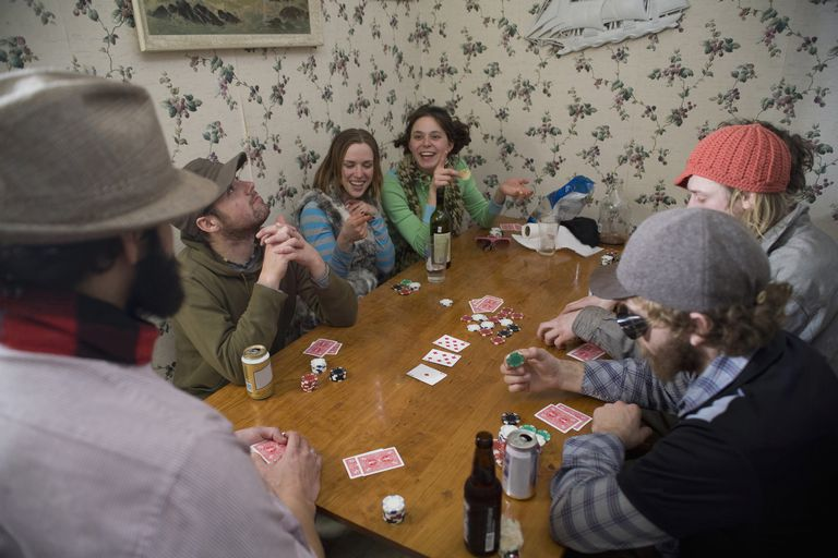 Young adults playing poker at big wooden table
