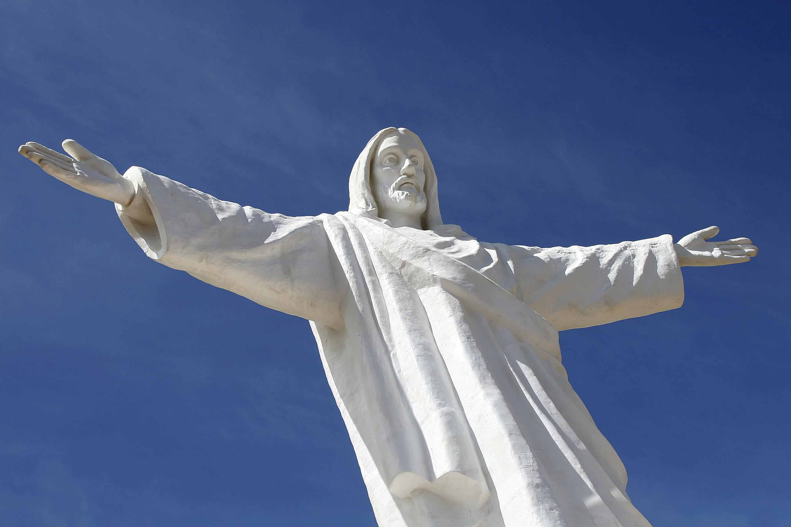 A statue of Christ with his arms out wide