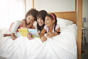 Mother & 2 kids reading story in bed