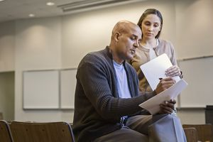 Professor and student reviewing document in lecture hall