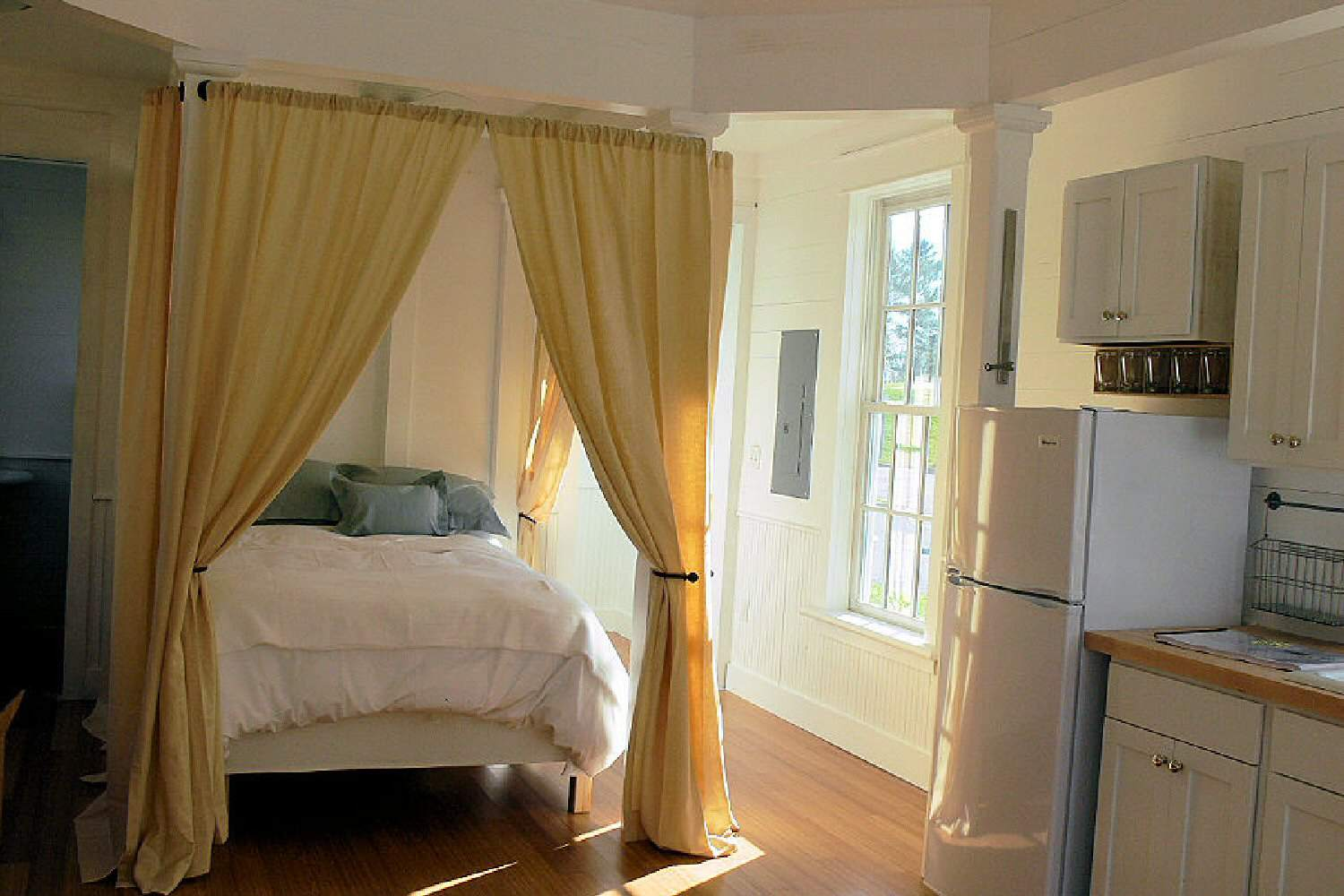 bed with surrounding curtains near a large window on the same wall as the built-in kitchen