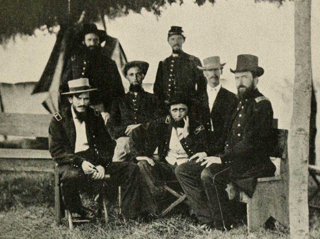 Benjamin H. Grierson seated in blue Union Army uniform surrounded by his staff officers.
