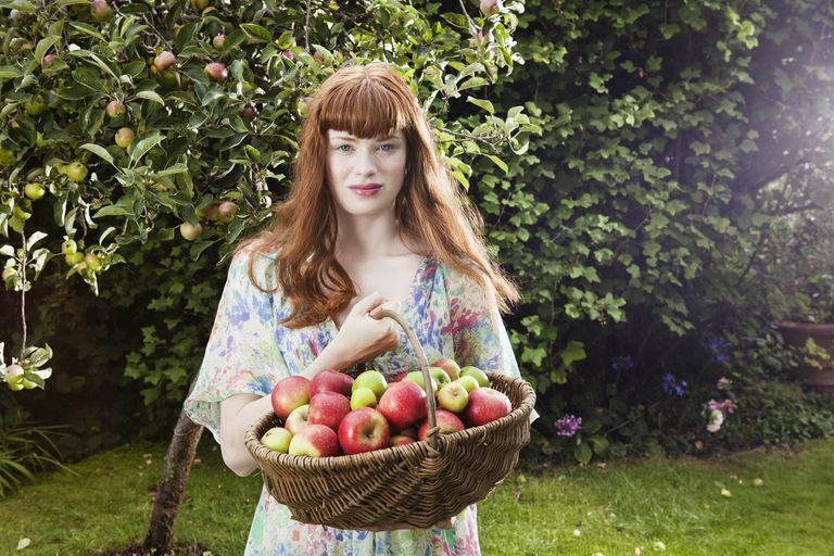 Woman holding basket with apples.