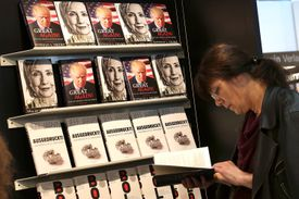 A woman looks at a book in front of a display showing books by Donald Trump and Hillary Clinton