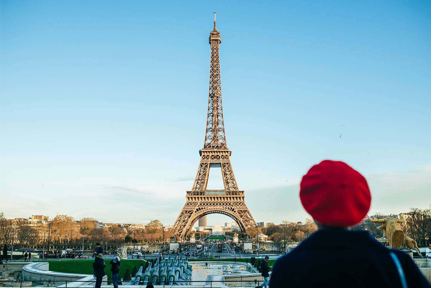 View of Eiffel Tower with back view of young woman standing in the foreground
