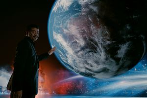 Neil DeGrasse Tyson in front of a projection of Earth
