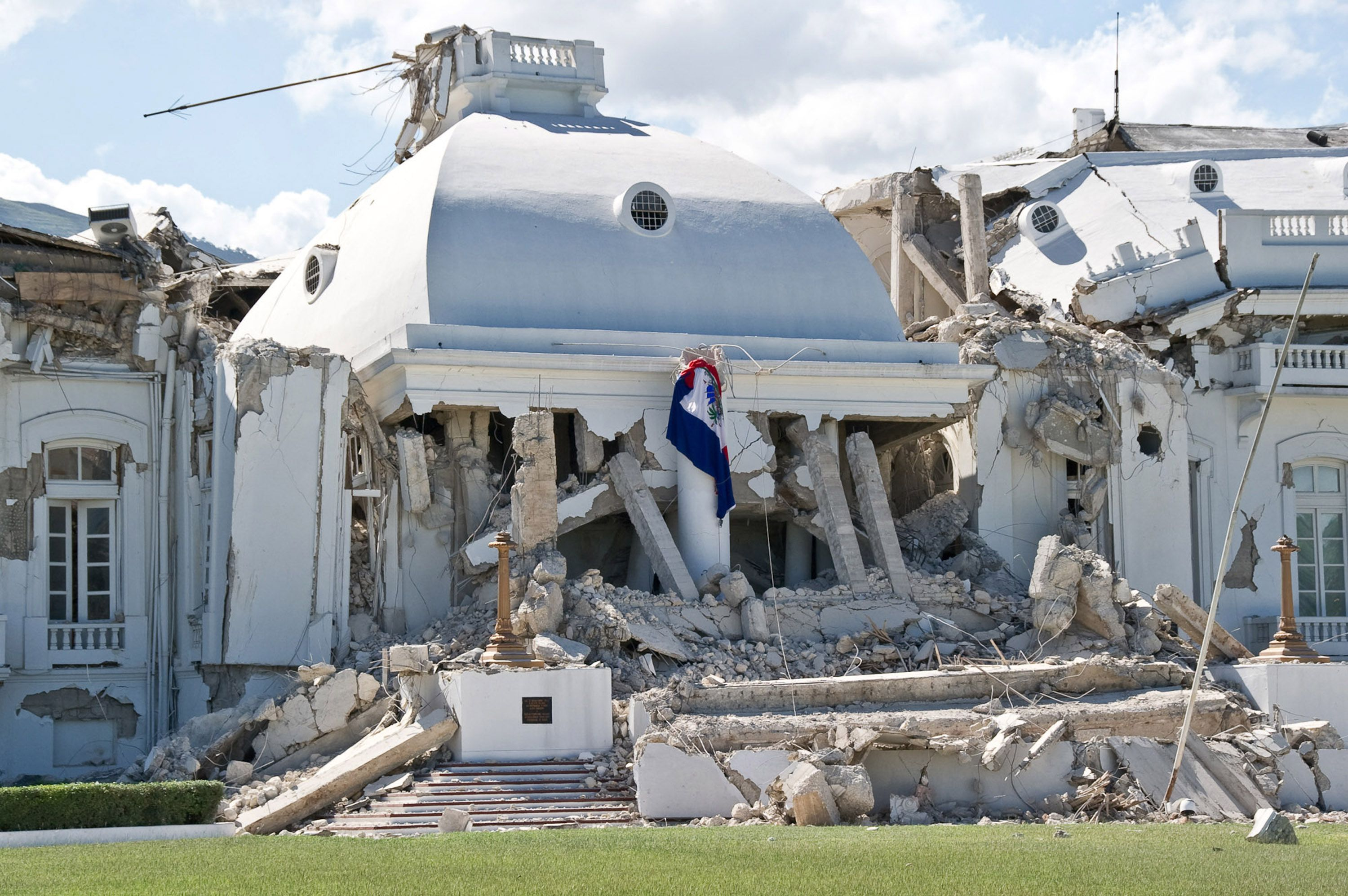 Haitian flag hangs on the ruins of a building after an earthquake