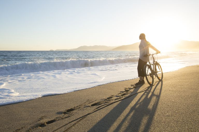 Female bicyclist on a beach at sunrise