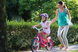 Mother helping daughter to ride bicycle in park.