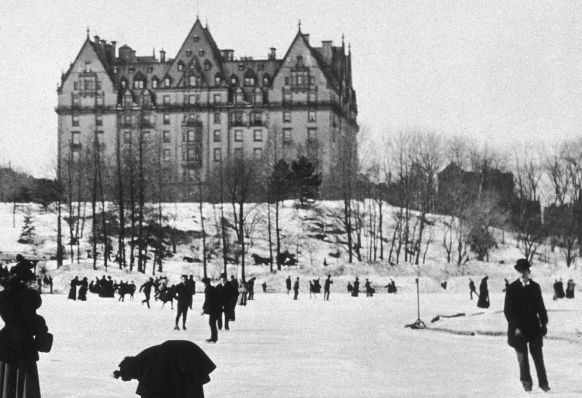 Historic black and white photo of mansion overlooking ice skaters in Central Park, 1894