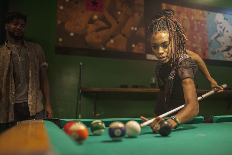 A young woman playing pool