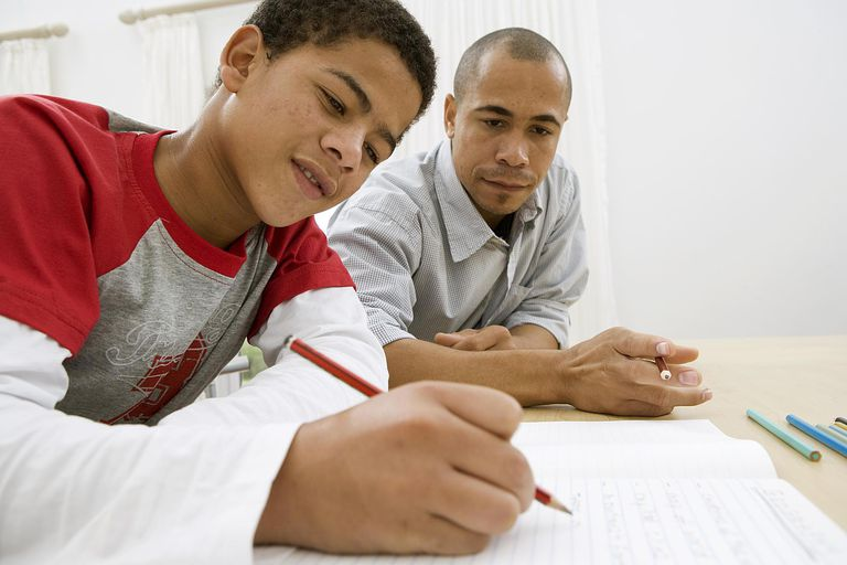 Boy doing homework with his dad