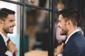 businessman adjusting tie and smiling in mirror