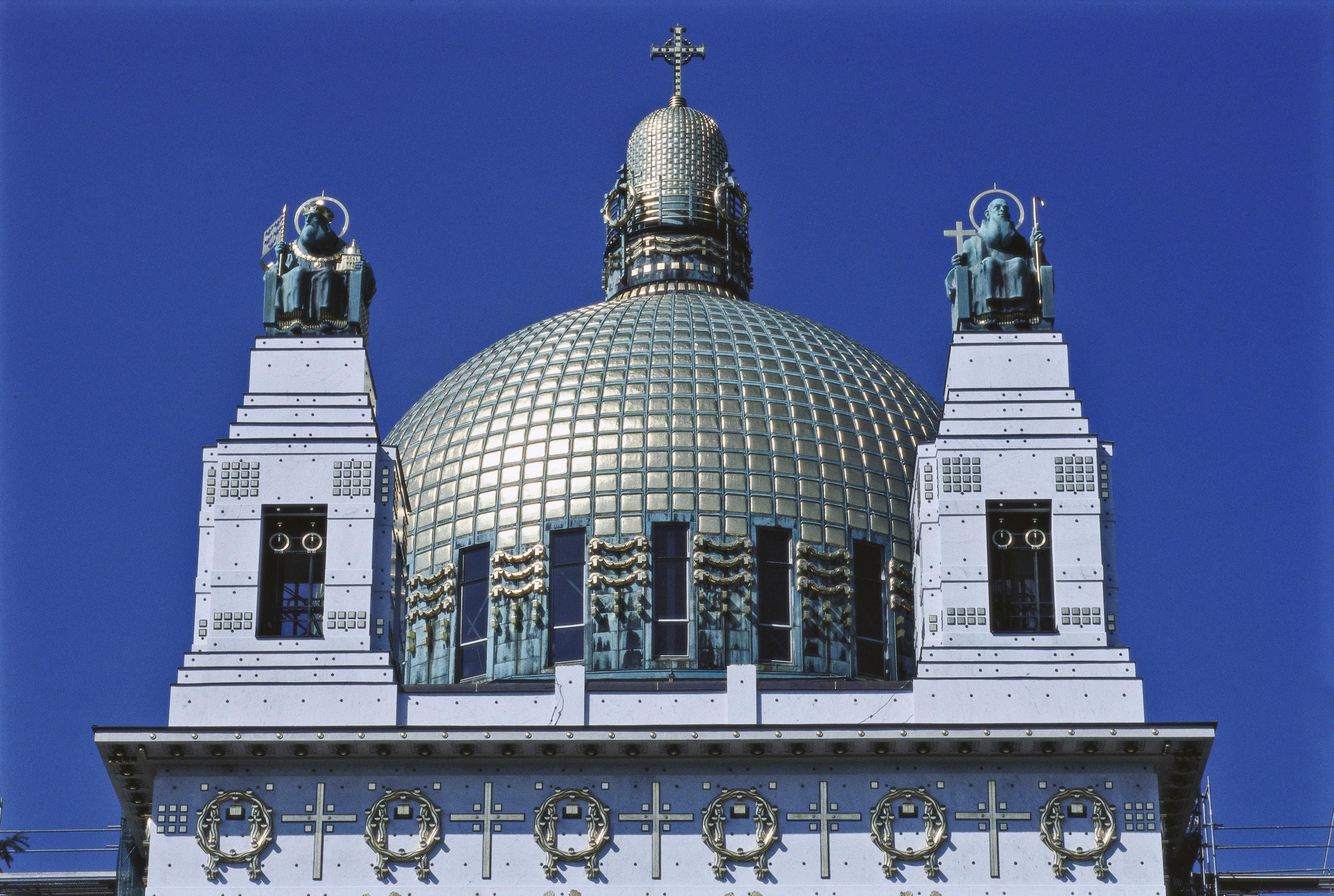 ornate dome with cupola and cross surrounded by two statues on ornate, pyramid pedestals