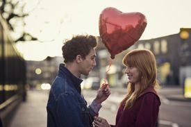 Couple with heart-shaped balloon gazing at each other during dusk.