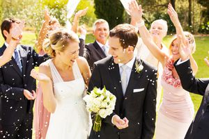 Guests Throwing Confetti On Couple During Reception In Garden