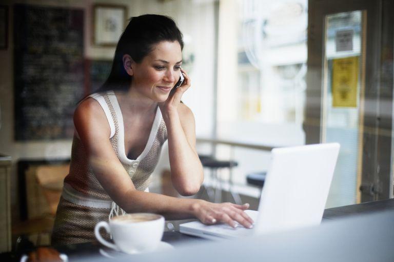 Muchacha hispana al teléfono delante de pantalla computadora.