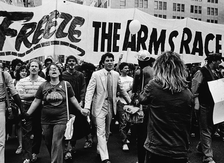 "Photographs of demonstrators walking hand-in-hand under a banner reading ""Freeze the arms race"""