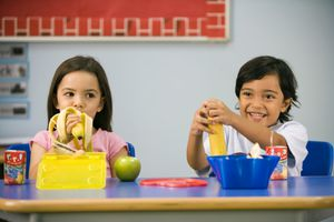 A boy and girl having lunch in a classroom.