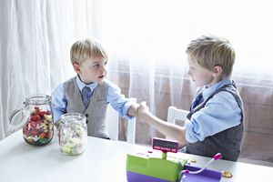 Two well-dressed kids play store with a fake cash register