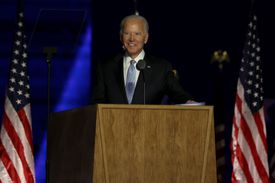Joe Biden stands behind a wood podium, with American flags behind him on either side